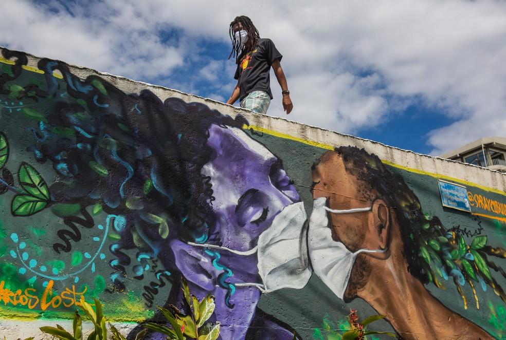 15 de abril: na foto, homem com máscara de proteção para a Covid-19 passa por grafite de duas pessoas se beijando de máscara em Salvador. — Foto: Antonnelo Veneri/AFP