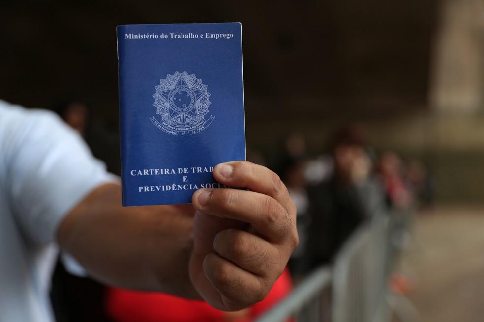 Trabalhador segura carteira de trabalho — Foto: Amanda Perobelli / Reuters