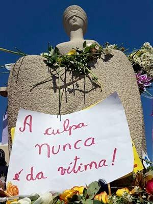 Estátua da Justiça, em frente ao STF, com flores e cartaz dizendo que a culpa nunca é da vítima  (Foto: Raquel Ribeiro/Arquivo pessoal)
