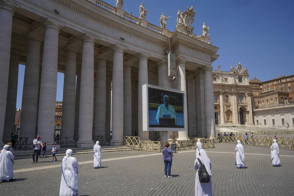 Freiras praticam distanciamento social enquanto acompanham transmissão de fala do Papa Francisco em telão no Vaticano — Foto: Andrew Medichini/AP