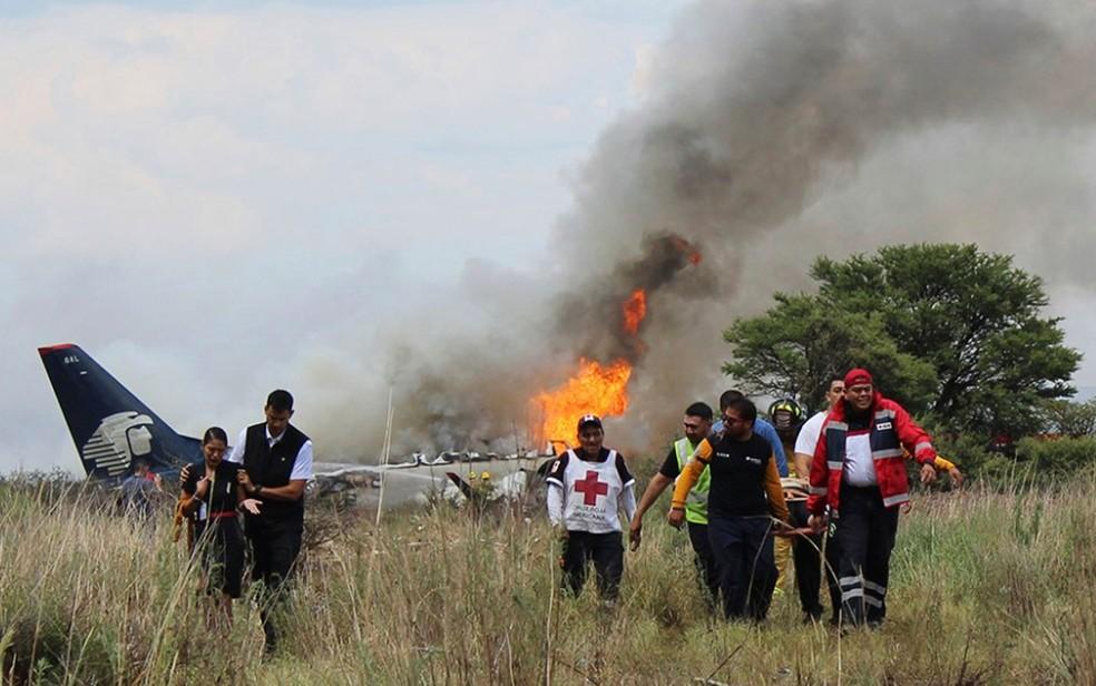 Socorristas carregam ferido em maca durante resgate após acidente com avião da Aeroméxico perto do aeroporto de Durango, no México, na terça-feira (31) (Foto: Red Cross Durango via AP)