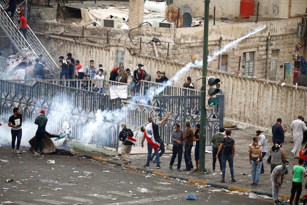 Um manifestante joga uma lata de gás lacrimogêneo durante um protesto contra corrupção, falta de emprego e serviços ruins, em Bagdá, nesta sexta ( — Foto: Reuters/Thaier Al-Sudani