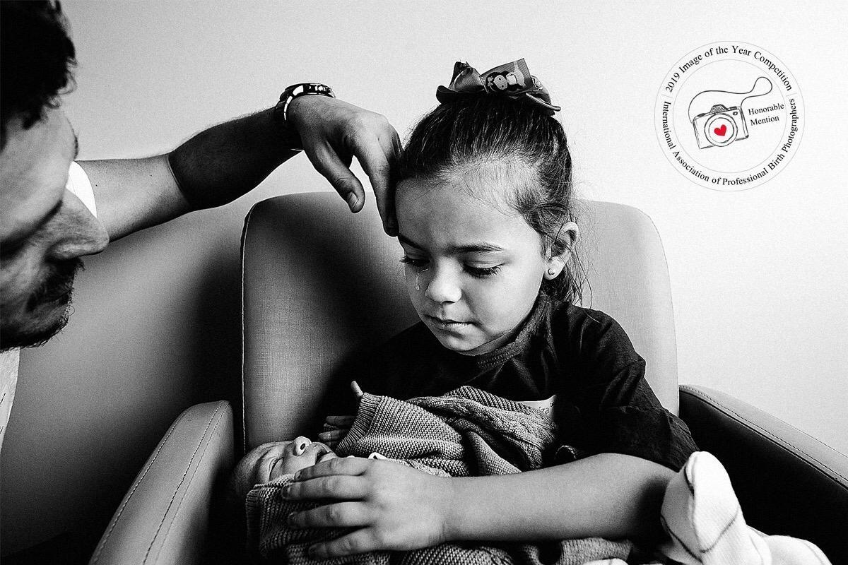 Ceci, 6 anos, segurando seu irmão no colo pela primeira vez (Foto: Bárbara Aviz)