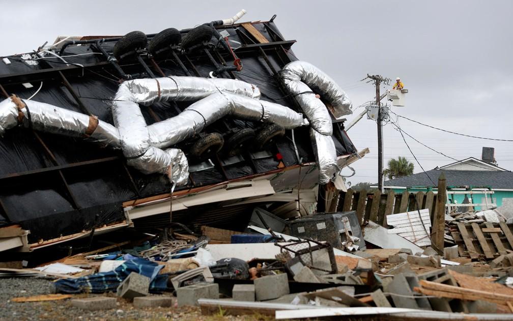 Funcionário de companhia de energia trabalha para consertar sistema em Emerald Isle, na Carolina do Norte, na quinta-feira (5) — Foto: AP Photo/Tom Copeland