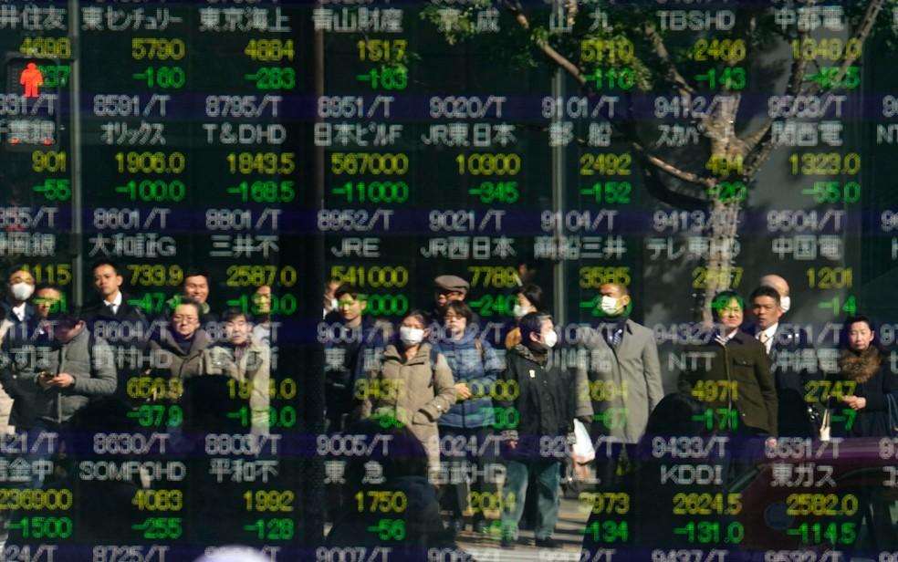 O reflexo de pessoas é visto em um indicador eletrônico de uma bolsa de valores em Tóquio, no Japão. As ações na Ásia caíram nesta terça-feira (6) após um dia selvagem para os mercados dos EUA, que resultou na maior queda na média industrial Dow Jones em seis e meio ano (Foto: Shizuo Kambayashi/AP)
