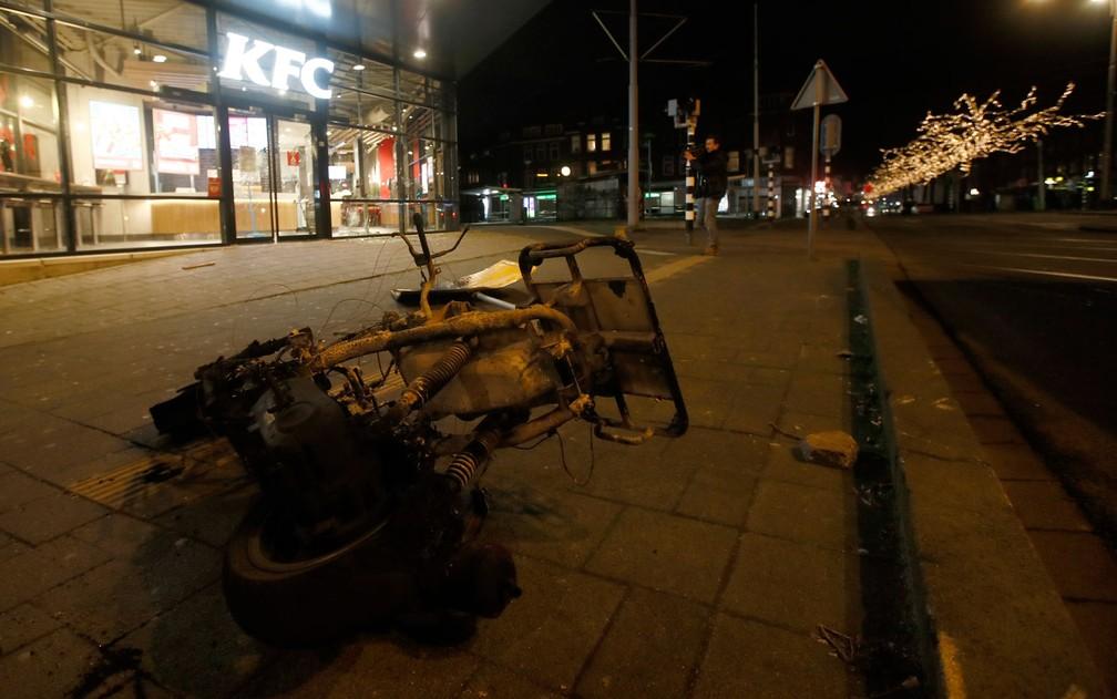 Restos de moto incendiada durante protesto contra toque de recolher em Roterdã, na Holanda, na segunda-feira (25) — Foto: AP Photo/Peter Dejong