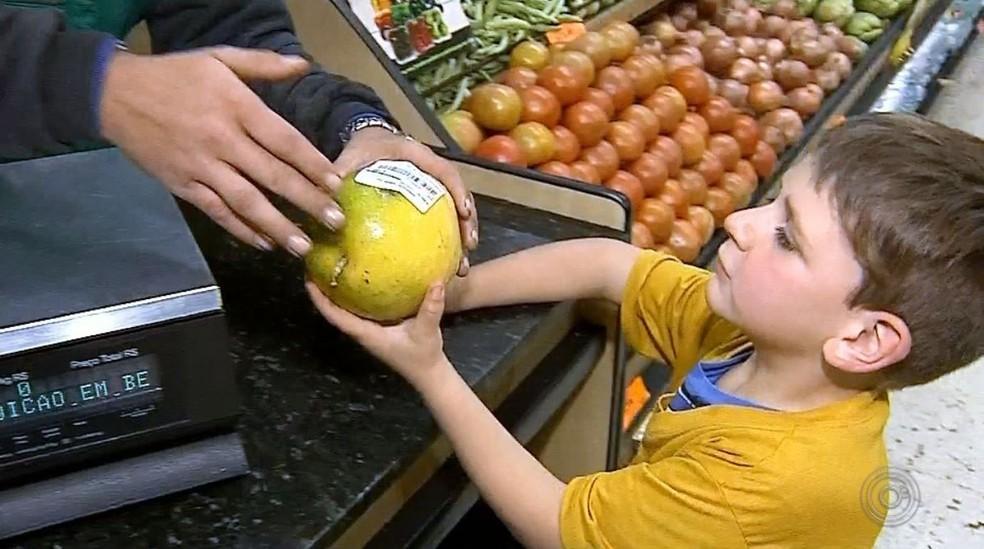 Mesmo quem levou apenas um produto para casa, como o garoto Pedro Santi, ficou feliz com a compra — Foto: TV TEM/Reprodução