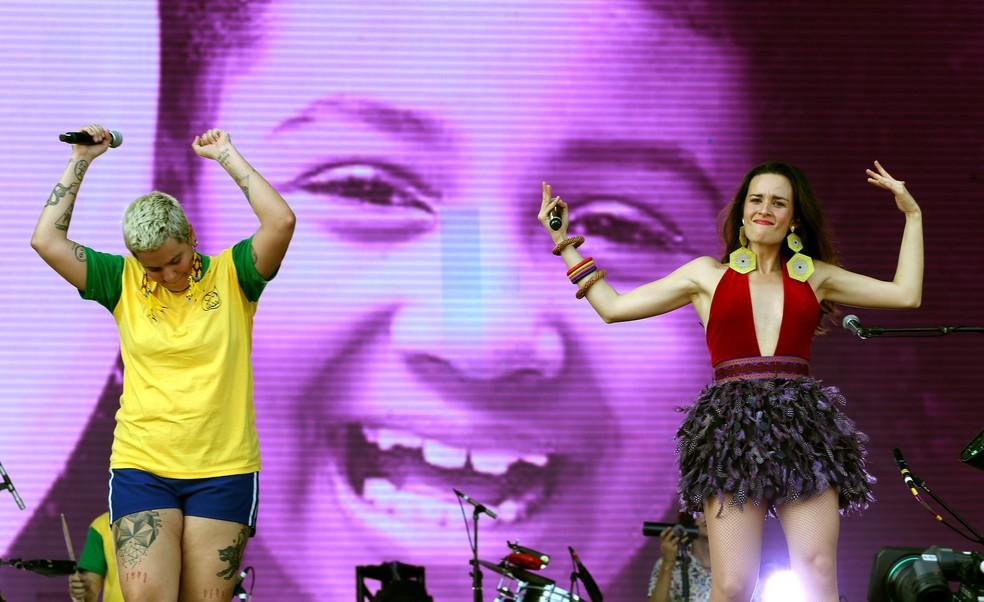 Juliana Strassacapa, da banda Francisco el Hombre, e Catalina García, do grupo Monsieur Periné, tendo ao fundo uma foto em homenagem a menina Ágatha Felix em show no Rock in Rio nesta quinta-feira (3) — Foto: WILTON JUNIOR/ESTADÃO CONTEÚDO