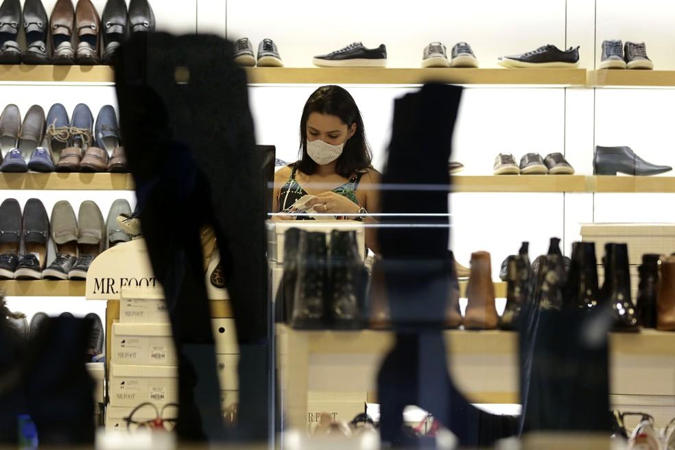 27 de maio de 2020 - Funcionária de loja de sapatos usa máscara em um shopping center de Brasília durante a pandemia do novo coronavírus no Brasil — Foto: Eraldo Peres/AP