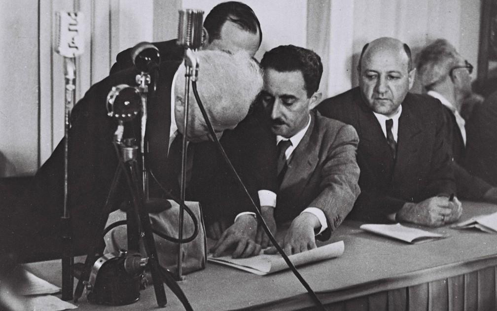 David Ben-Gurion (esquerda) assina a Declara�?§�?£o de Independ�?ªncia de Israel, enquanto Moshe Sharett segura o documento e Eliezer Kapla observa, no museu de Arte de Tel Aviv, em 14 de maio de 1948 (Foto: Israel Government Press Office)