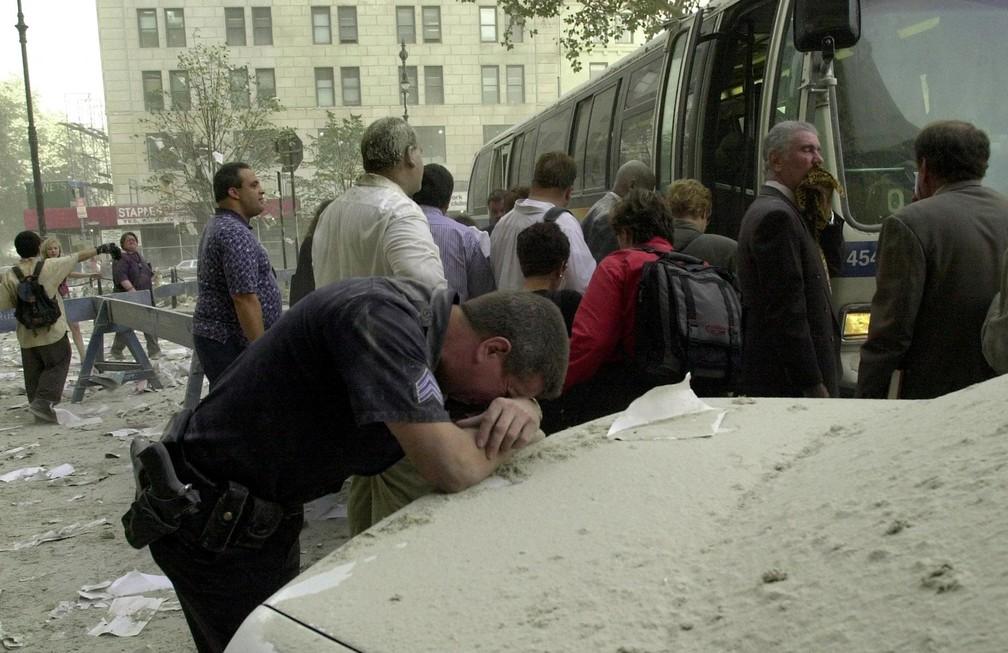 Exausto, um policial apoia a cabeça na traseira de um carro para descansar após a queda das torres do World Trade Center em 11 de setembro de 2001 — Foto: Stan Honda/AFP/Arquivo