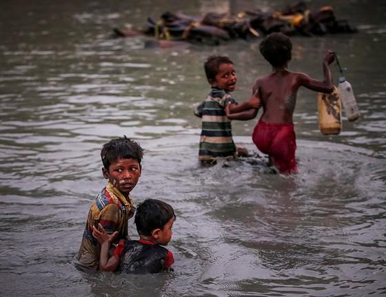 Irmãos rohingyas se seguram enquanto atravessam o Rio Naf, na fronteira entre Bangladesh e Mianmar (Foto: FOTÓGRAFOS/REUTERS)