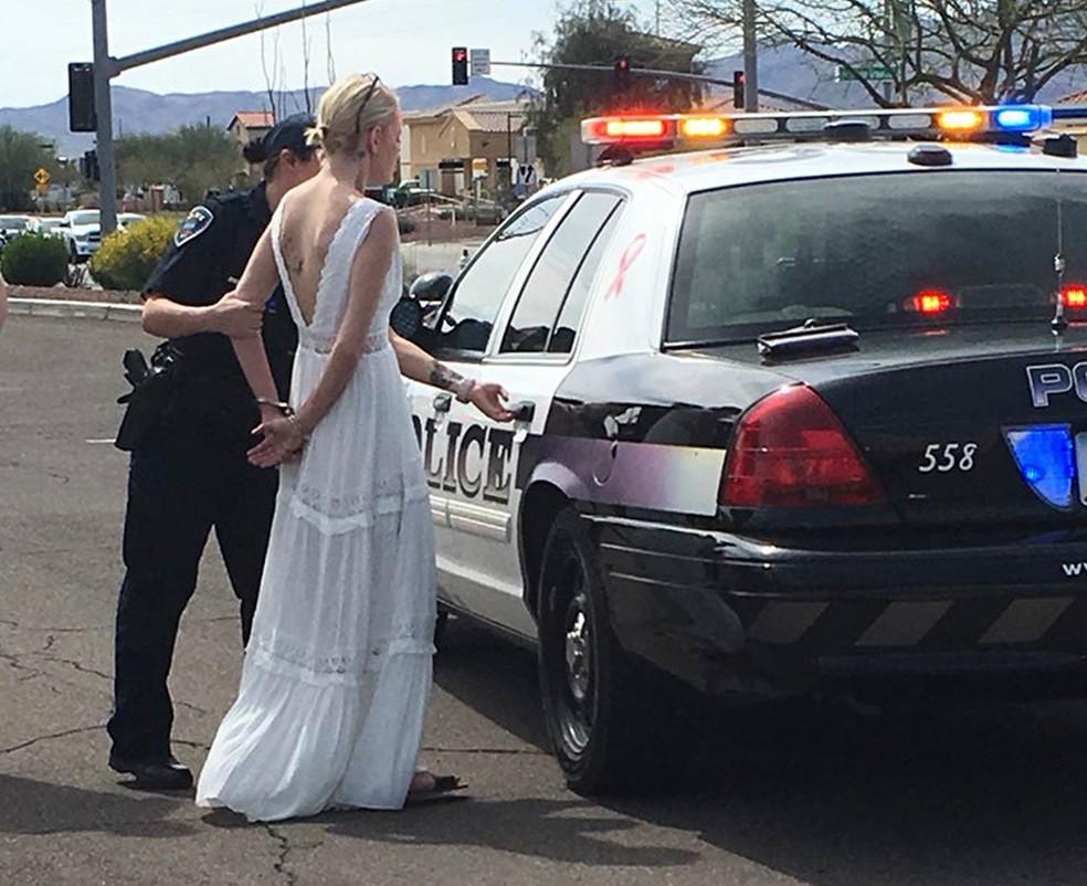 Foto divulgada pela polícia mostra a noive, algemada, sendo levada à delegacia para fazer exame de sangue (Foto: Marana Police Department/via AP)