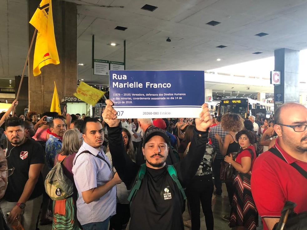 Manifestante segura placa com nome da rua Marielle Franco em ato na rodoviária do Plano Piloto, em Brasília — Foto: Nicole Angel/ G1