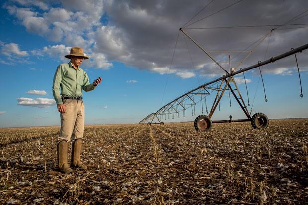 Amilton Costa, da SLC, usa o GPS para identificar áreas com maior produtividade da fazenda, em Goiás. À direita, uma máquina de irrigação move-se sozinha pelo campo, comandada por um algoritmo (Foto: Paralaxis)