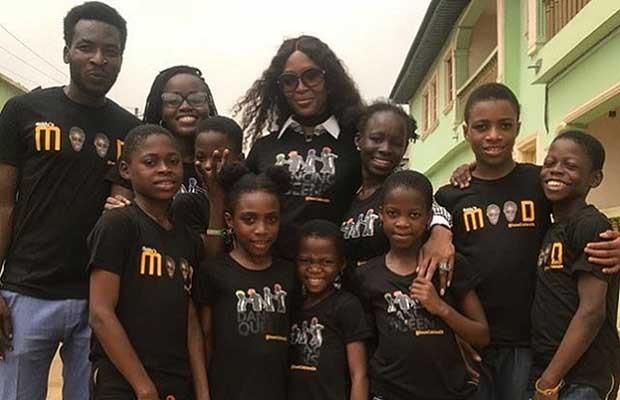 Naomi Campbell com as crianças do projeto e Seyi Oluyole, ao seu lado, de óculos (Foto: Reprodução)