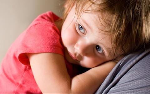 Criança triste ou doente no colo da mãe (Foto: Shutterstock)
