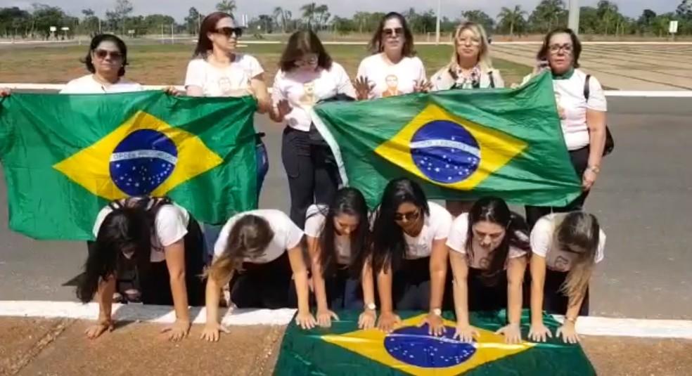 Grupo de 'bolsonarianas' oram com a bandeira do Brasil durante visita a Brasília — Foto: Reprodução/Redes sociais