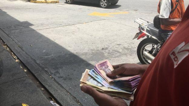 Muita gente paga pelo combustível com notas de dinheiro, mas a moeda local tem pouco valor (Foto: Reprodução/BBC)