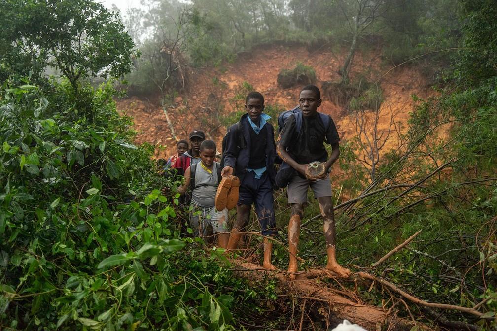 Alunos de uma escola de St. Charles Luanga resgatados por militares após a passagem do ciclone Idai atravessam ponto de um deslizamento em uma rodovia de Chimanimani, na província de Manicaland, no Zimbábue — Foto: Zinyange Auntony/AFP