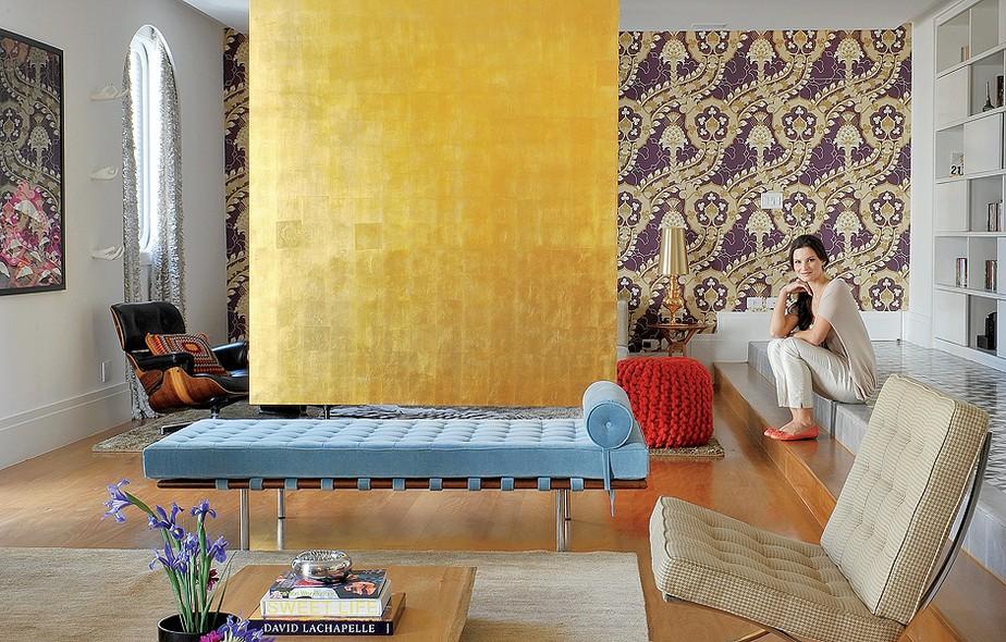 A sala deste apartamento decorado por Marcelo Rosenbaum tem um painel de destaque folheado de ouro por João Migotto. Ele esconde fios de aparelhos eletrônicos