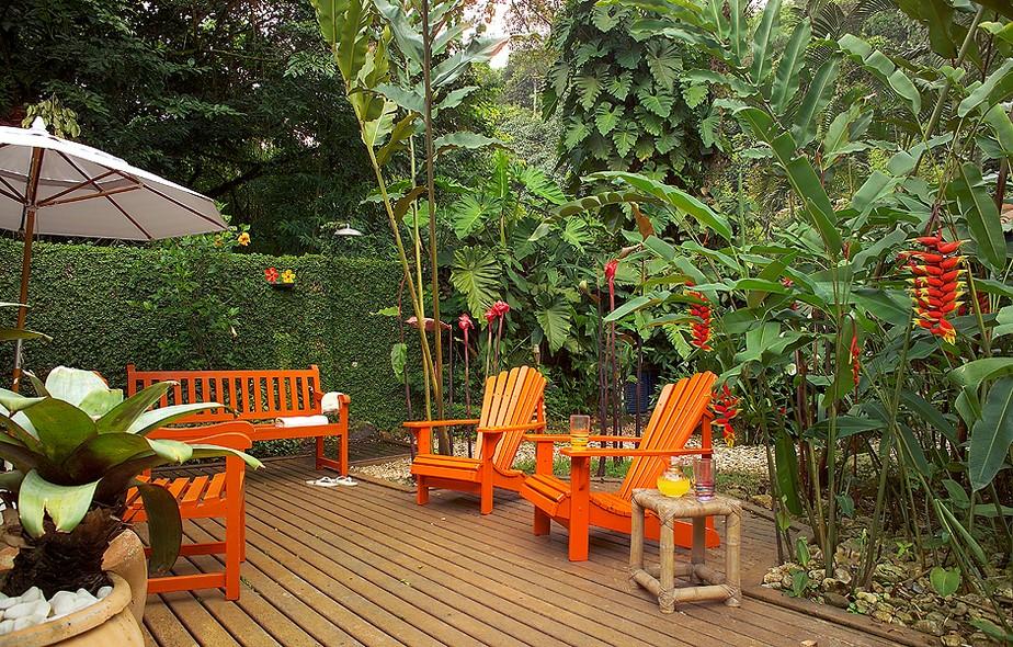 Este deque de madeira, com jardim projetado pela paisagista Cynthia Azevedo, tem móveis na cor laranja que contrastam com os tons vibrantes das helicônias e dos hibiscos. Projeto dos arquitetos Alice Martins e Flávio Butti