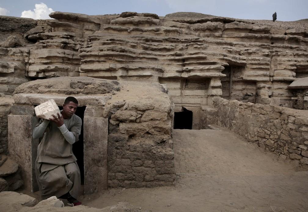 Trabalhador carrega um artefato para fora da tumba na necrópole. — Foto: Nariman El-Mofty/AP