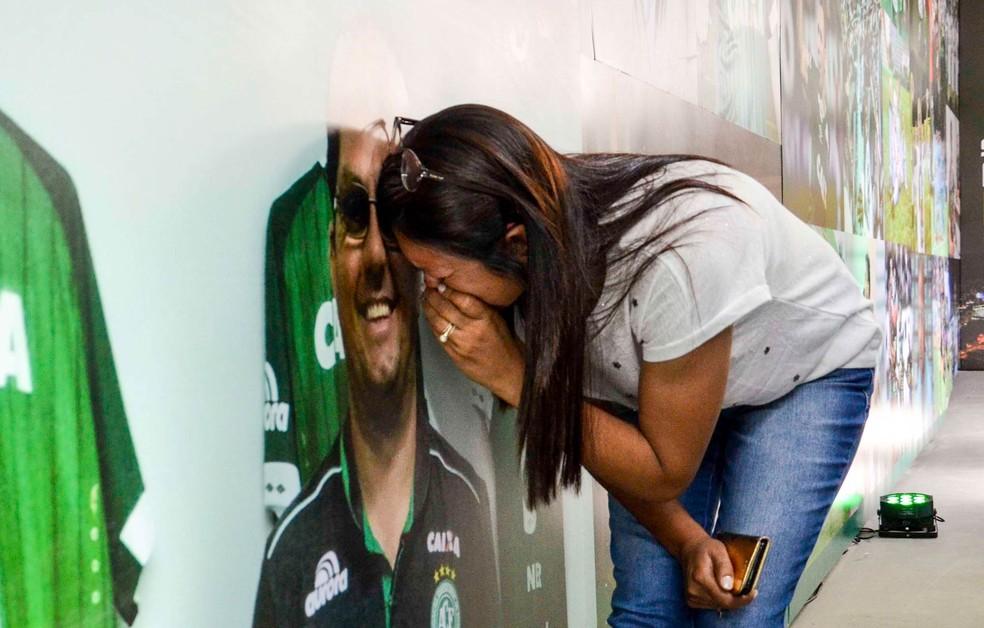 Mulher se emociona diante de uma foto no túnel de acesso ao vestiário da equipe da Chapecoense na Arena Condá, em Chapecó (SC), aberto para visitação no dia que marca um ano do acidente aéreo que tirou a vida de grande parte da equipe (Foto: Tarla Wolski/Futura Press/Estadão Conteúdo)