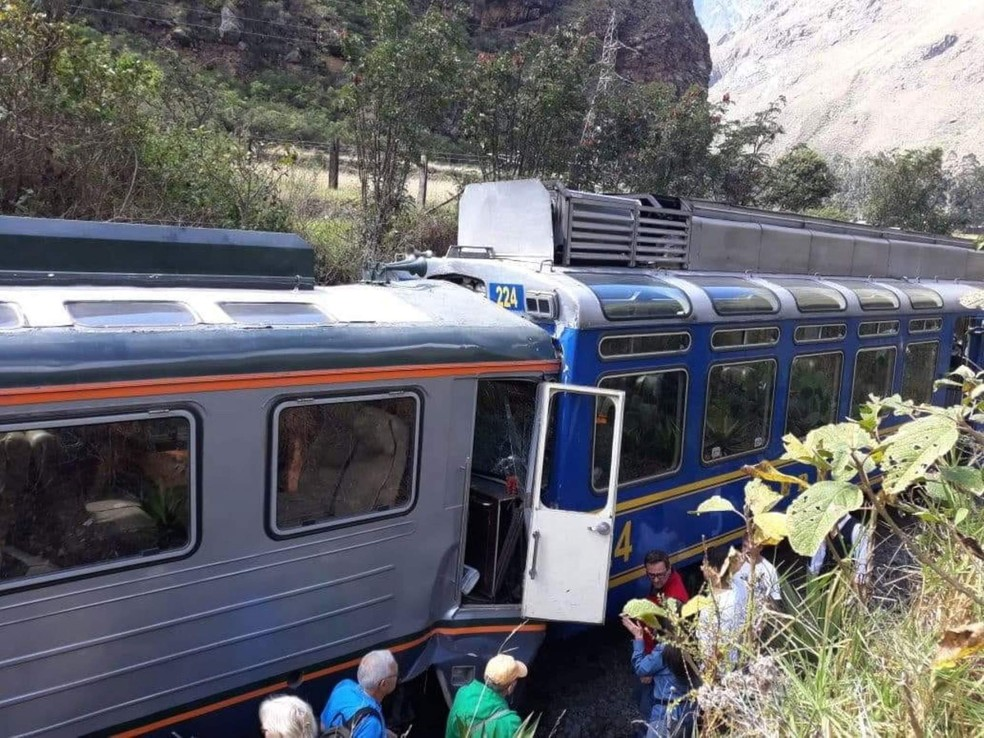 Passageiros observam trens que colidiram nesta terça-feira (31) na estrada que dá acesso a Machu Picchu, no Peru (Foto: Andina News Agency via AP)