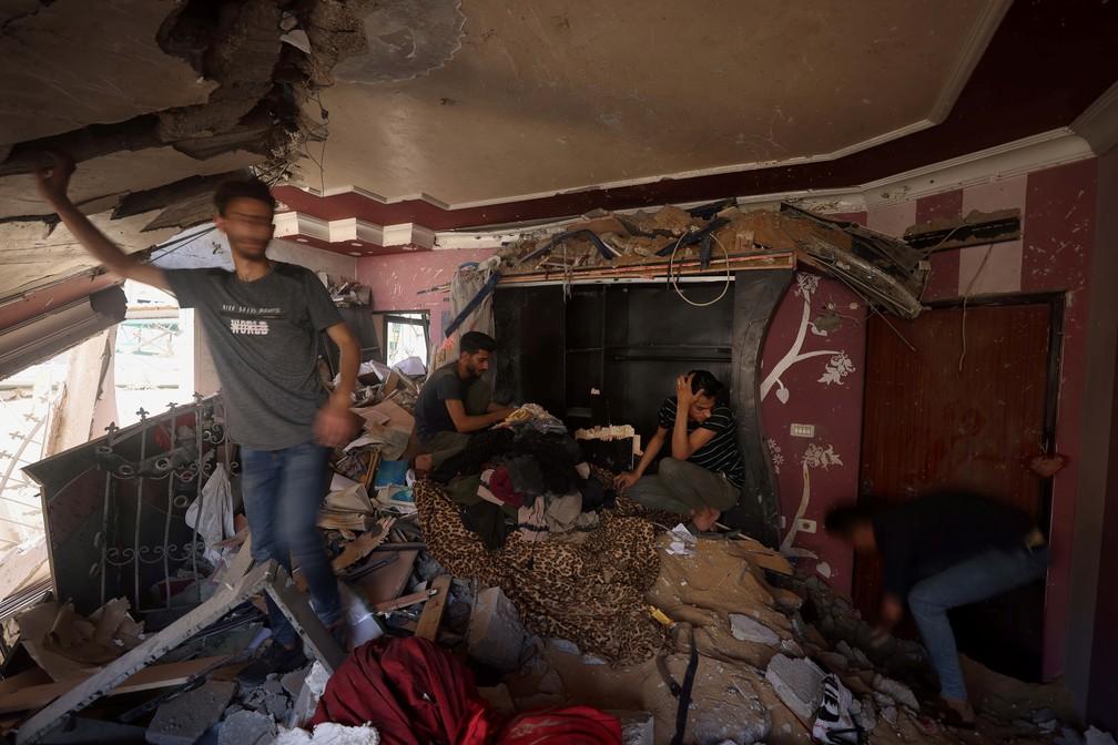 Palestinos inspecionam os danos após ataques aéreos israelenses na Cidade de Gaza nesta segunda (17)   — Foto: Mohammed Salem/Reuters