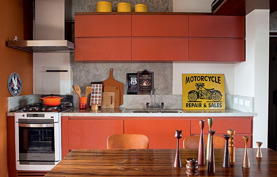 Parede e marcenaria laranja alegram a cozinha, de arquitetura rústica e masculina. Projeto do arquiteto Gustavo Calazans