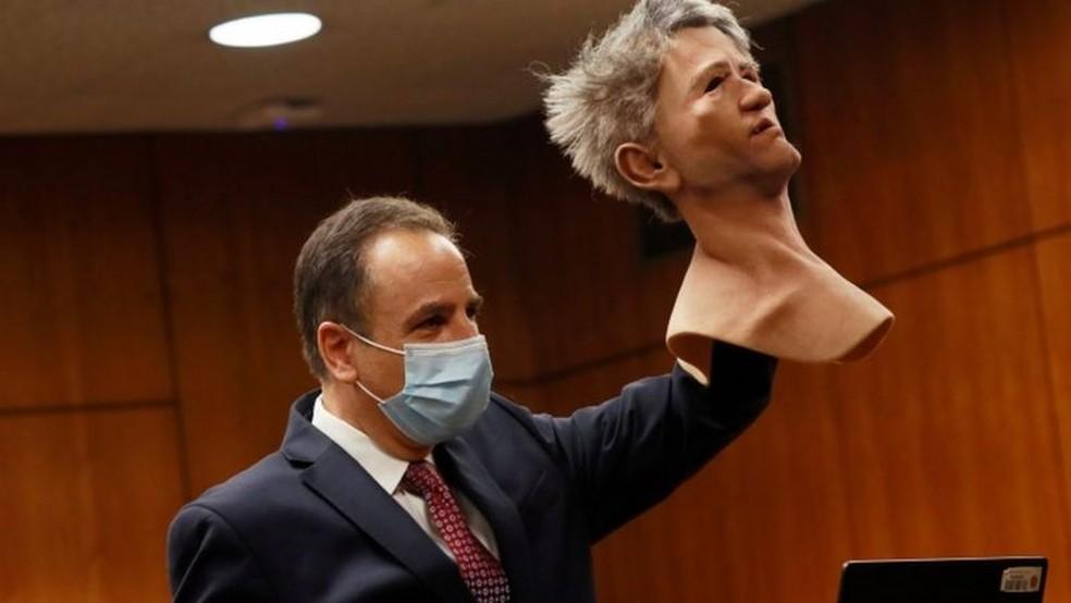 O procurador Habib A. Balian mostra uma máscara usada por Robert Durst quando a polícia o prendeu — Foto: Reuters/BBC