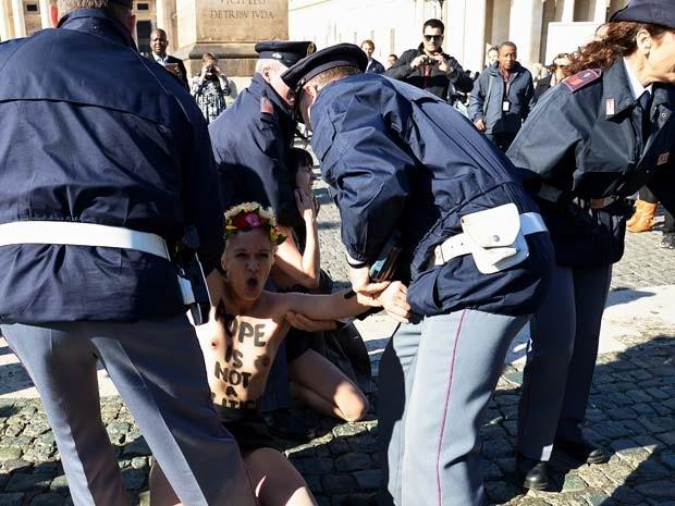Ativista do Femen é detida por policiais após protesto no Vaticano contra a visita do Papa Francisco a Estrasburgo (Foto: AFP PHOTO / ALBERTO PIZZOLI)