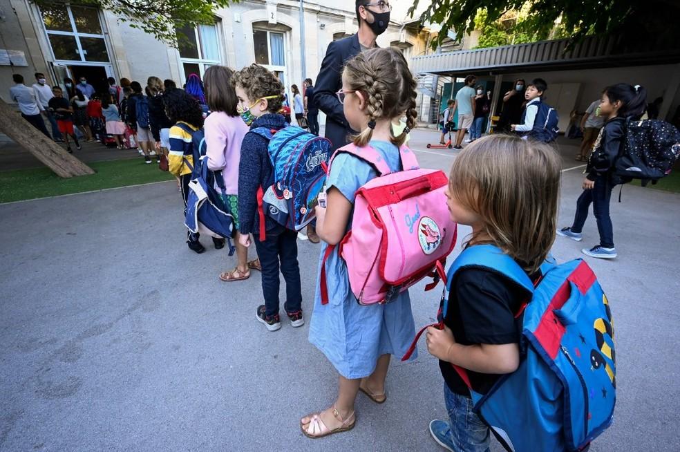 Crianças com mochilas esperam em fila em um parquinho de uma escola primária em Montpellier, na França, no dia 1º de setembro — Foto: Pascal Guyot / AFP