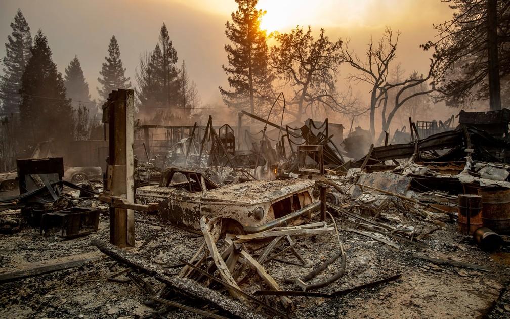 Um carro antigo queimado é visto entre escombros após ser atingido pelo incêndio Camp Fire, em Paradise, na Califórnia, na quinta-feira (8) — Foto: AP Photo/Noah Berger