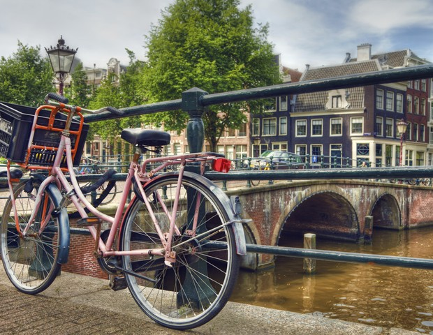Pink Parked Bicycle Beside a Canal in Amsterdam (Foto: Getty Images/iStockphoto)