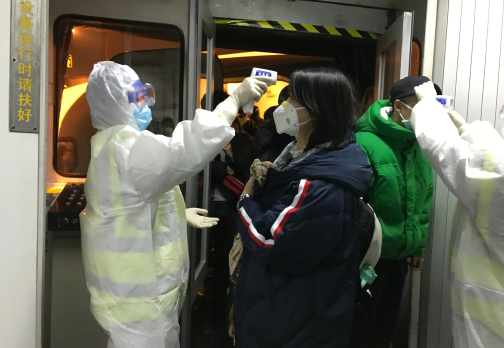 Funcionários de saúde medem temperatura corporal de passageiros que chegam da cidade de Wuhan ao aeroporto de Pequim, em 22 de janeiro, em meio ao surto de coronavírus na China — Foto: AP Foto Emily Wang