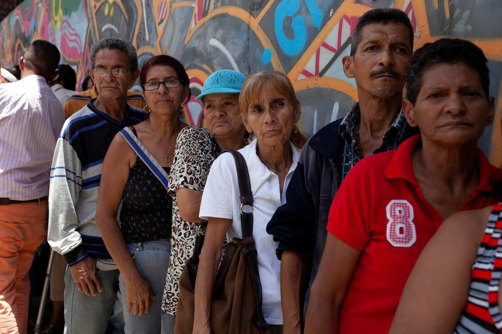 Pessoas fazem fila do lado de fora de um supermercado em Caracas, na Venezuela (Foto: Adriana Loureiro/Reuters)