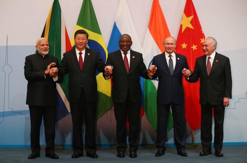 Michel Temer (dir.) e os outros presidentes do Brics, bloco formado por Brasil, Rússia, Índia, China e África do Sul, posam de mãos dadas durante o 10º encontro do grupo de economias emergentes em Joanesburgo, na África do Sul (Foto: Mike Hutchings/Pool via AFP)