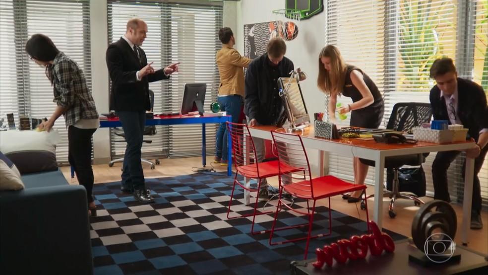Rodrigo (Paulo Tiefenthaler) rearruma a sala de Beto (João Baldasserini) - 'Haja Coração' — Foto: Globo