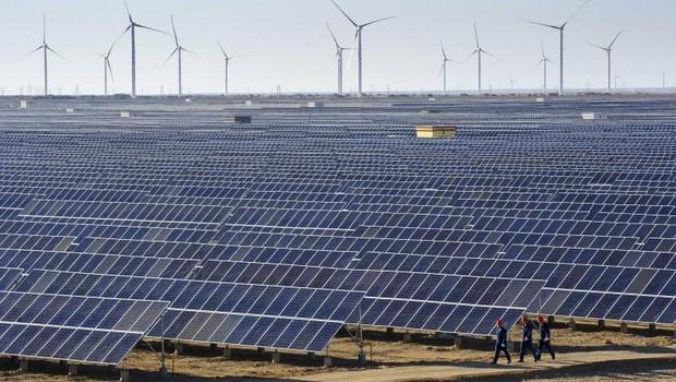 Trabalhadores passam por painéis solares e turbinas eólicas em uma das muitas usinas que produzem energia renovável na China (Foto: Arquivo/Reuters)