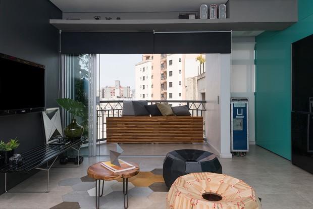 VARANDA | O banco é ripado e de madeira nogueira, feito pela marcenaria Móveis Evolution. As almofadas são da Cinerama.  (Foto: Manu Oristanio)