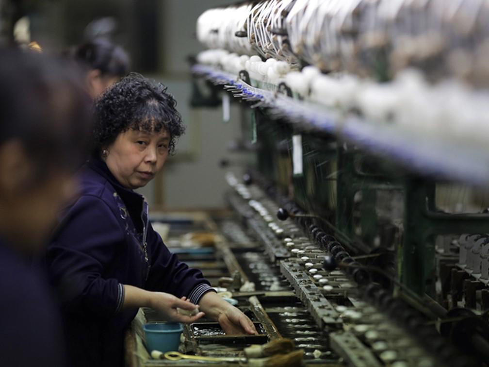 Mulher trabalha em fábrica de seda na província chinesa de Jiangsu.  — Foto: Andy Wong/AP