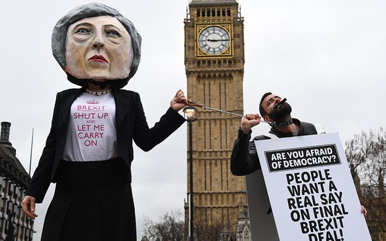 Manifestante com boneco da primeira-ministra Theresa May, em protesto em frente ao Parlamento britânico em Londres (Foto: AFP PHOTO/JUSTIN TALLIS)