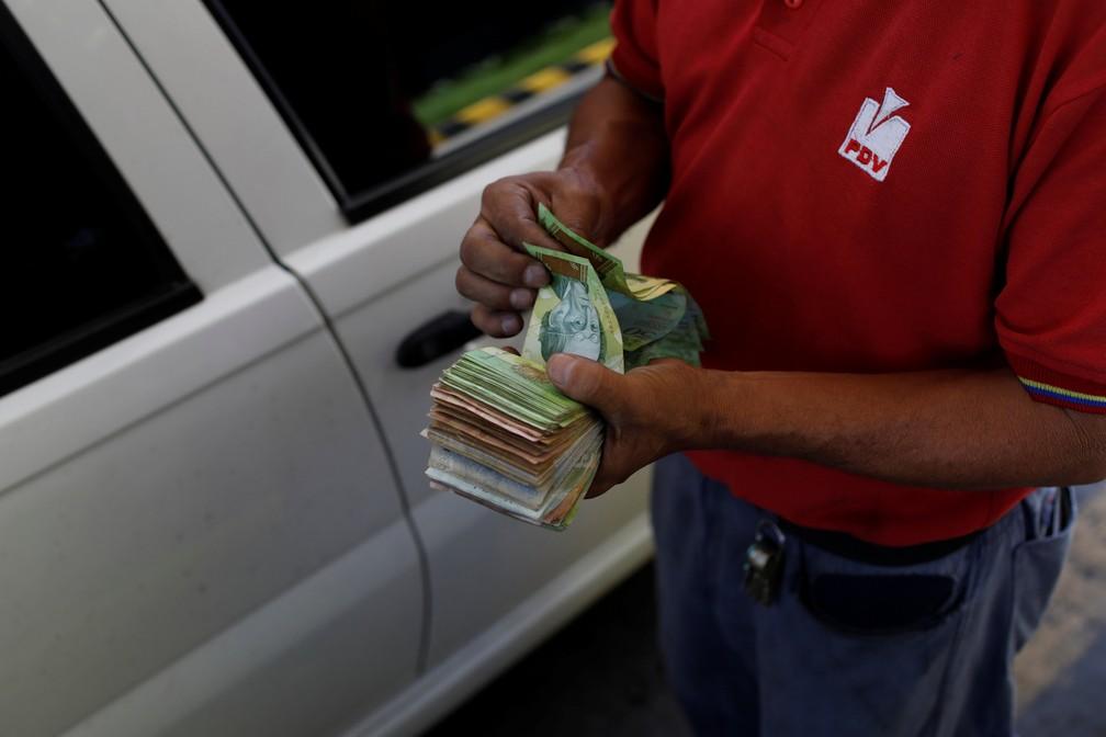 Funcionário de posto de gasolina conta dinheiro na Venezuela, dias antes da mudança da moeda no país (Foto: Marco Bello/Reuters)