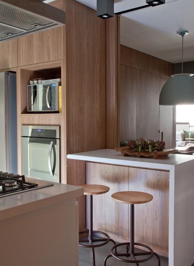 Para seguir integrado ao restante da área social, o trecho da cozinha mais próximo da sala repete os acabamentos em tom de madeira (Foto: Luís Gomes)