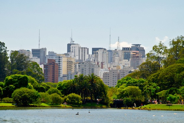 Buildings of city of Sao Paulo, seen over tops of green trees and pond with geese at Ibirapuera Park. (Foto: Getty Images)