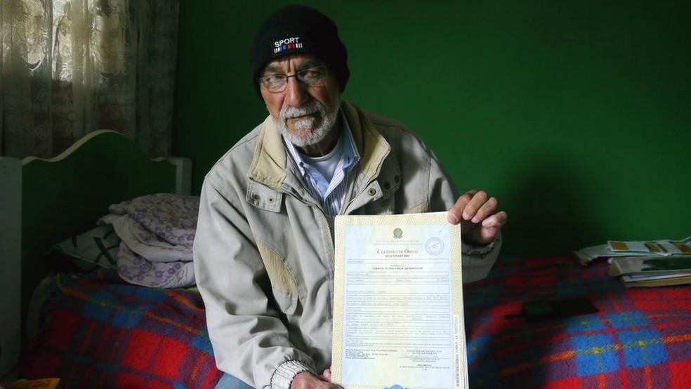 Leonardo da Cruz, pai de Robson, mostra a certidão de óbito do filho, ainda com a inscrição 'desaparecido' — Foto: Amanda Rossi/BBC