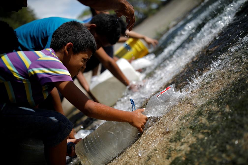 Criança capta água de esgoto que corre para o leito do Rio Guaire, em Caracas, notoriamente poluído.  — Foto: Reuters/Carlos Garcia Rawlins