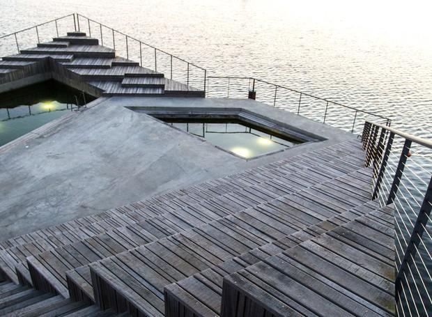 Detalhe do ponto de encontro Hasle Havsbad. A estrutura criada em um lago na Dinamarca conta com arquibancada para tomar sol e recortes no deque que criam pequenas piscinas (Foto: White Arkitekter/Divulgação)